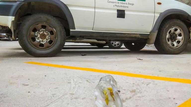 El vehículo junto a la botella con líquido inflamable que explotó.