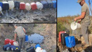 Padre e hijo cazadores sacan 120 cubos de agua de un pozo para que la fauna pueda beber