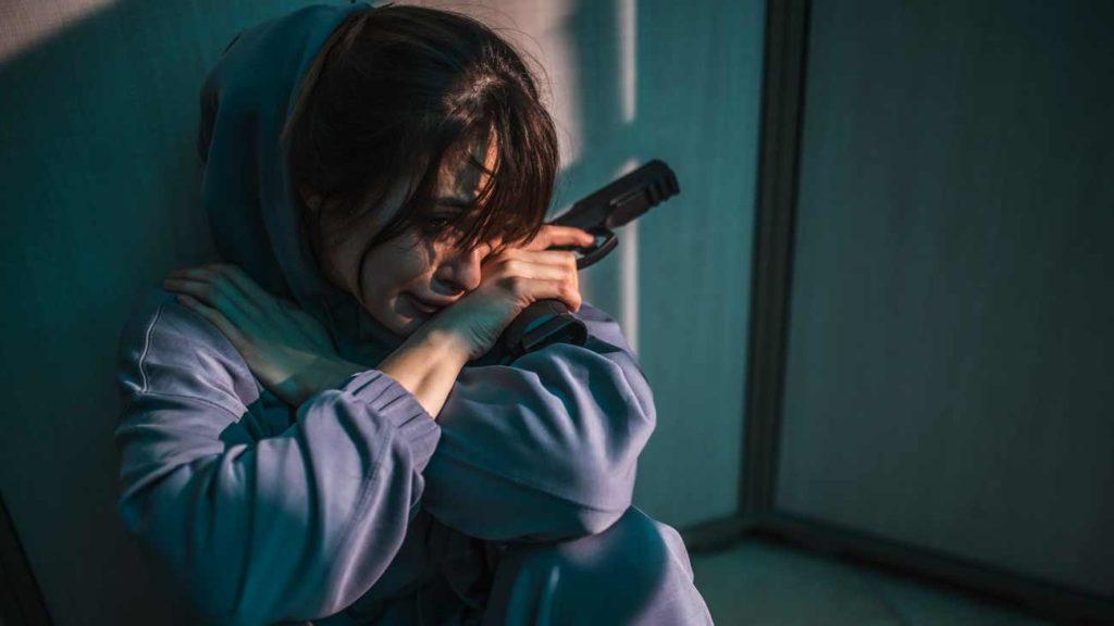 Una mujer, con una pistola. © Shutterstock