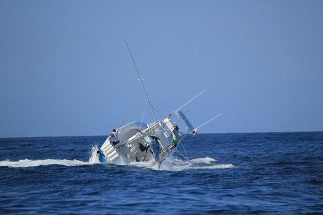 Uno de los tripulantes se aferra como puede a la embarcación mientras el pez sigue luchando / Foto Daily Mail