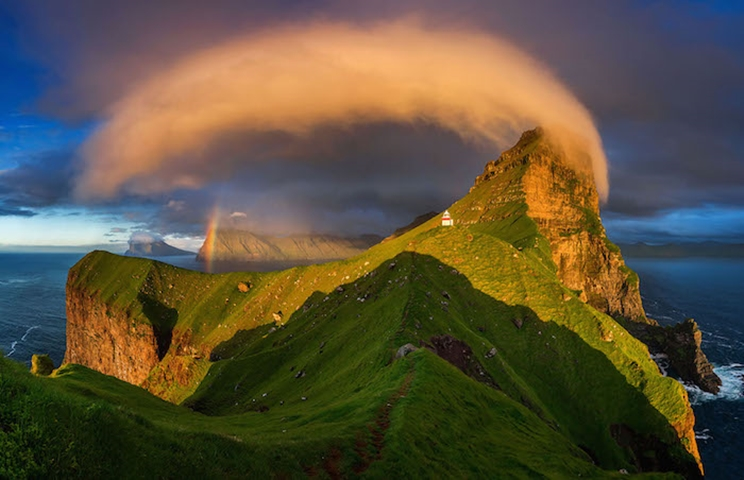 La puesta del sol ilumina un faro y arco iris en las Islas Feroe. / Fotografía: Infobae