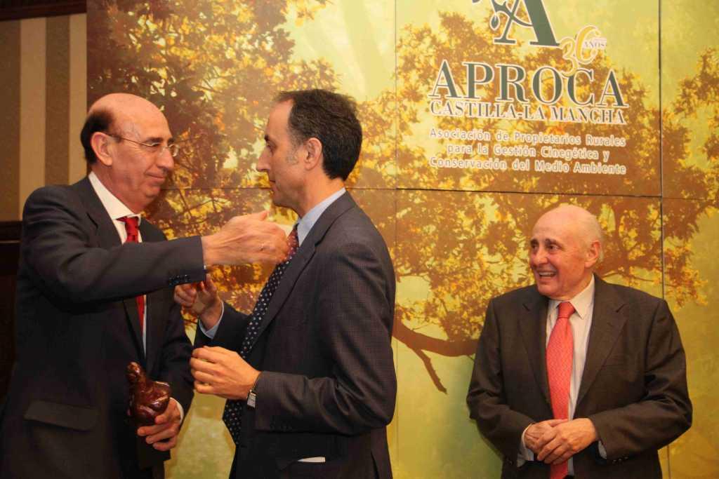 Juan Ramón Pérez del Hoyo recibe su reconocimiento de manos de Javier Gómez Elvira, ante la mirada de Ricardo Ayala
