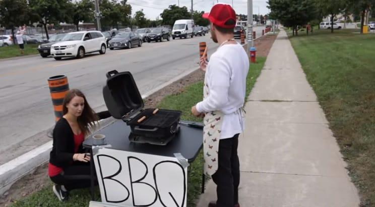 Un joven hace una barbacoa frente a una protesta de animalistas veganos