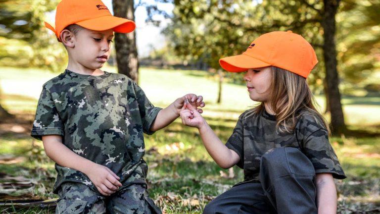 Dos niños examinan una pluma de perdiz en el campo. ©Angel Vidal