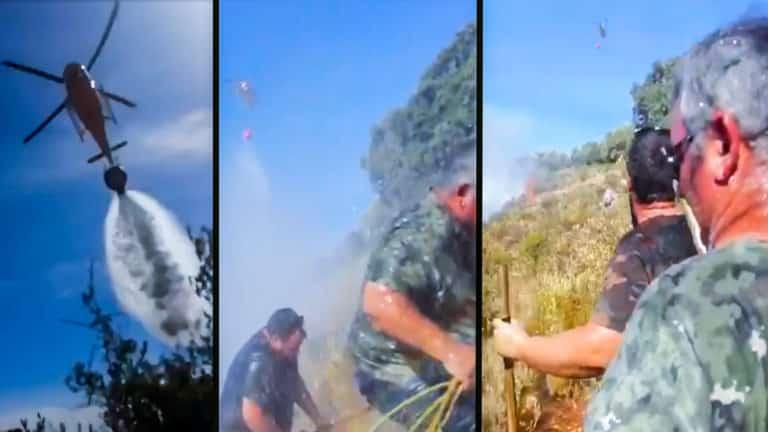 Los cazadores, en el momento de ser mojados por el helicóptero antiincendios.