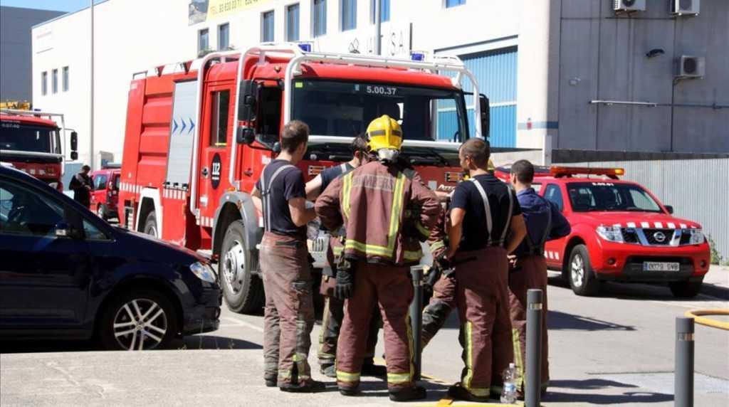 Grupo de bomberos en el exterior de la fábrica