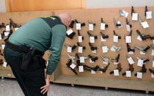 Un agente observa algunas de las armas expuestas en la comandancia y que salen a subasta. // R. V.